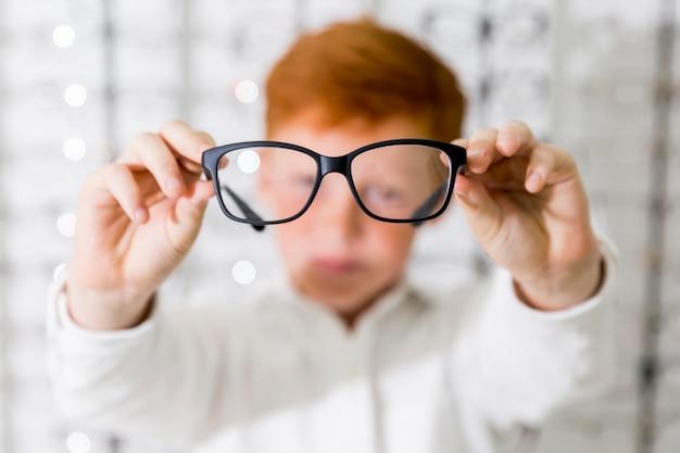 Close-up de menino mostrando óculos de armação preta na loja de óptica