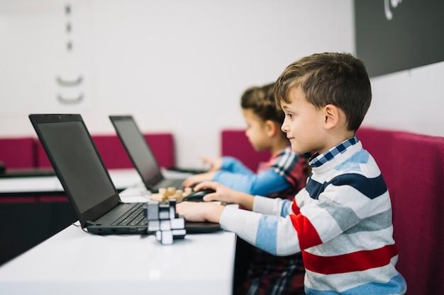 Close-up, de, menino, usando computador portátil, em, a, sala aula