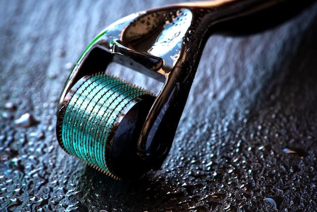 Close-up de mesoroller em um fundo preto com gotas da água.