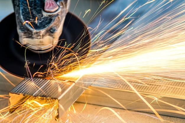 Close-up de metal de corte trabalhador com moedor. faíscas ao moer ferro.