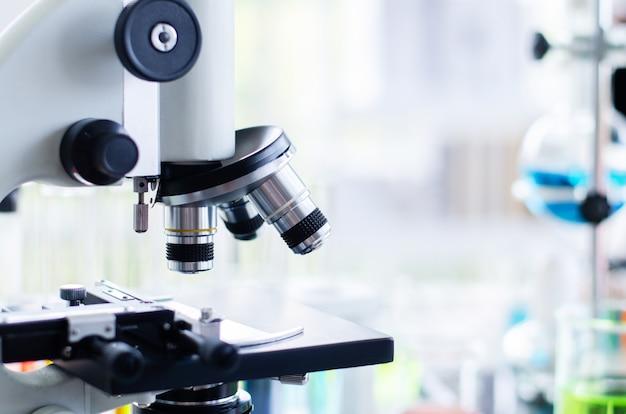 Close-up de microscópio com lente de metal no laboratório.