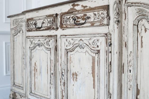 Close-up de mobiliário antigo gabinete branco cômoda com tinta descascada