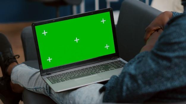 Close up de mock up display de laptop de tela verde no cara americano africano voltas sentado na cama na vida.