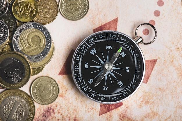 Close-up de moedas ao lado de uma bússola