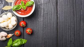 Close-up de molho de tomate com mussarela; massa; alho um manjericão na prancha de madeira