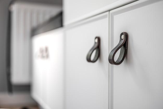 Close-up de móveis brancos minimalistas com alças pretas, detalhes de armário de cozinha