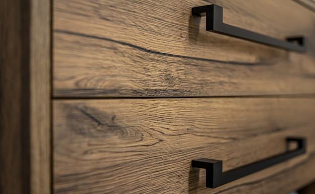 Close-up de móveis modernos de madeira escura com puxadores pretos.