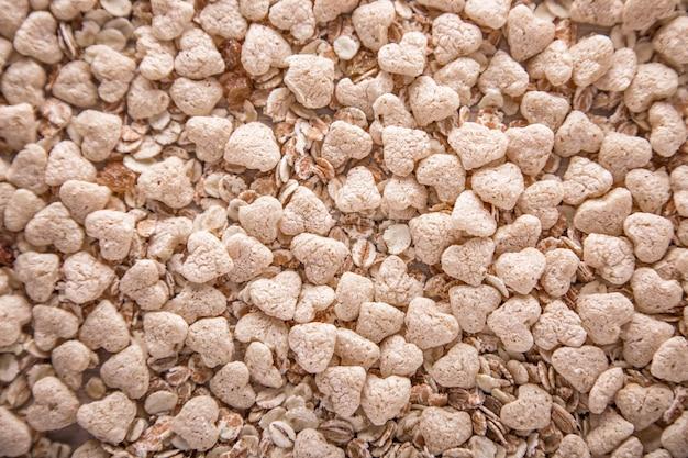Close-up de muesli seco em forma de coração. textura, superfície