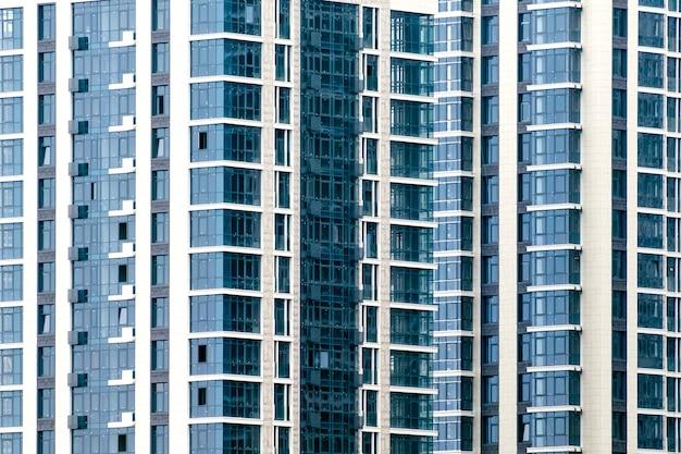 Close-up de muitas janelas na fachada de um novo prédio de apartamentos. para o fundo.