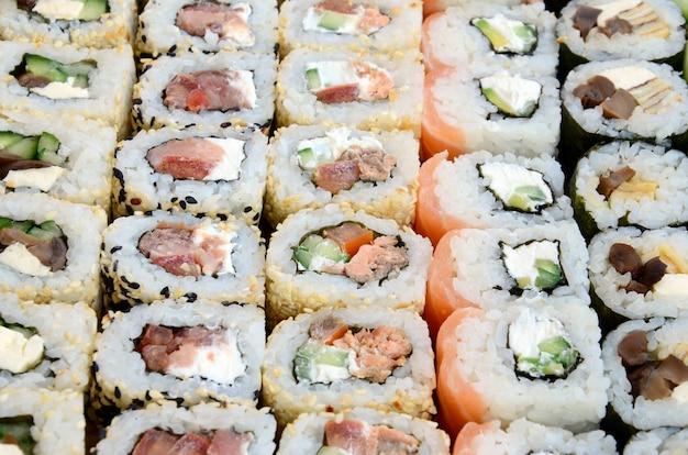 Close-up de muitos rolos de sushi com diferentes recheios