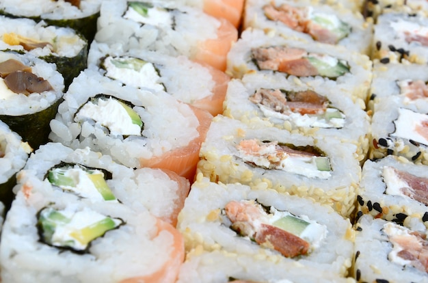 Close-up de muitos rolos de sushi com enchimentos diferentes.