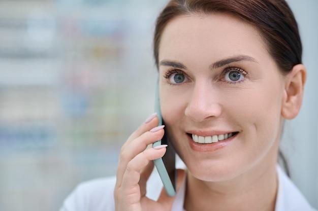 Close-up de mulher alegre com smartphone perto da orelha