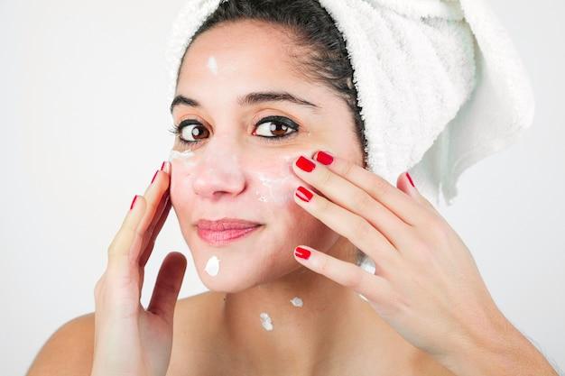 Close-up, de, mulher, aplicando, moisturizer, para, dela, rosto