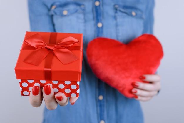 Close-up de mulher com caixa de presente e coração nas mãos isoladas
