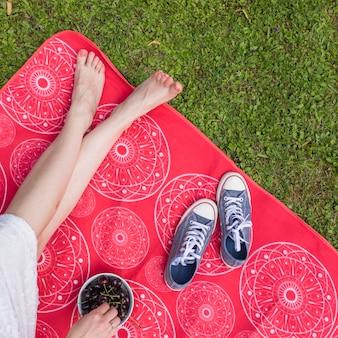 Close-up, de, mulher, com, cruzado pé, sentando, ligado, cobertor, segurando, cerejas