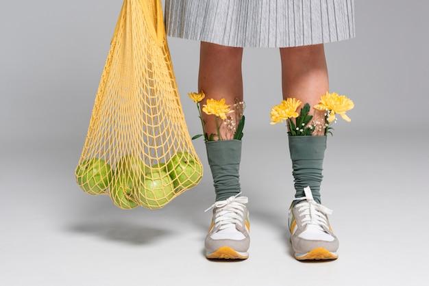 Close-up de mulher com flores em meias segurando uma bolsa de tartaruga