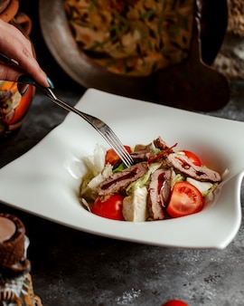 Close-up de mulher comendo salada de carne com alface, tomate e molho