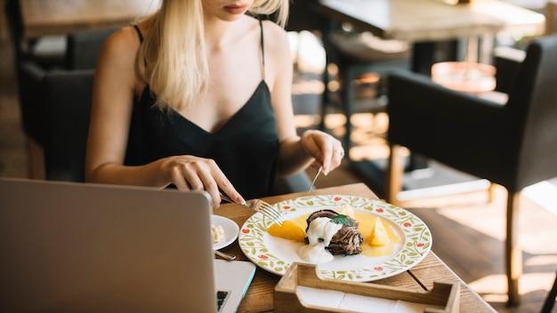 Close-up, de, mulher, comer, sobremesa, com, garfo, e, faca manteiga