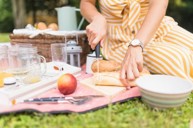 Close-up, de, mulher, corte pão, com, faca, ligado, piquenique