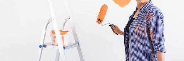 Close-up de mulher de meia-idade pintando a parede interior da casa. conceito de renovação, reparação e redecoração.