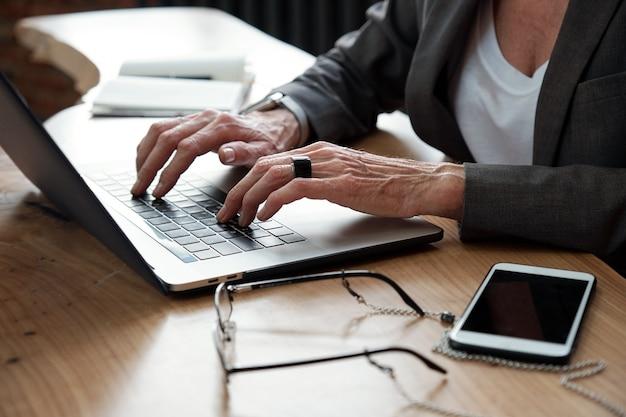 Close-up de mulher de negócios irreconhecível com anel sentado à mesa com smartphone e óculos e trabalhando em projeto online
