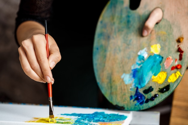 Close-up de mulher desenhando com tintas a óleo sobre tela