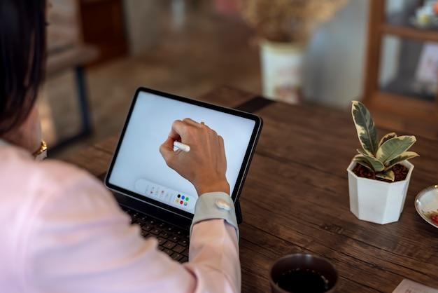 Close-up de mulher designer gráfica usando tablet digital enquanto trabalha