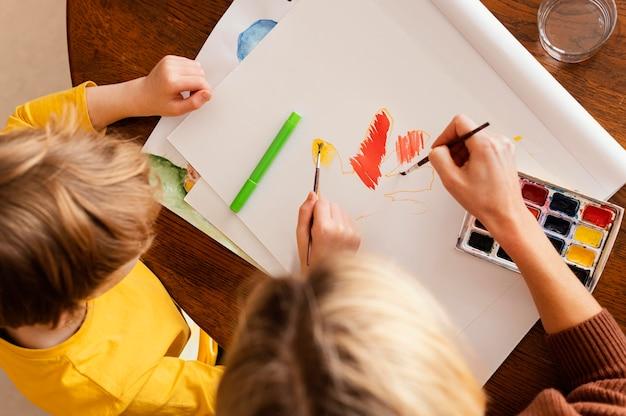 Close-up de mulher e criança pintando