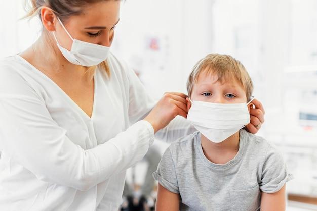 Close-up de mulher e criança usando máscara dentro de casa