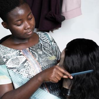 Close-up de mulher escovando cabelo de boneca
