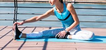 Close-up, de, mulher, esticar, dela, mão, e, perna, sentando, ligado, esteira exercício