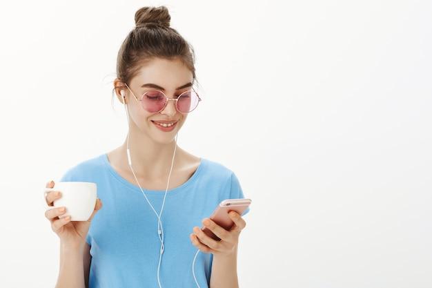 Close-up de mulher feminina elegante em óculos de sol, ouvindo podcast ou música, bebendo uma xícara de café, segurando um smartphone