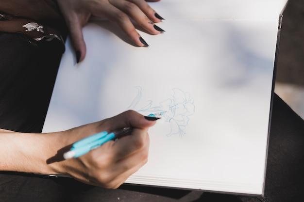 Close-up, de, mulher, flor desenho, com, azul coloriu, caneta, ligado, caderno