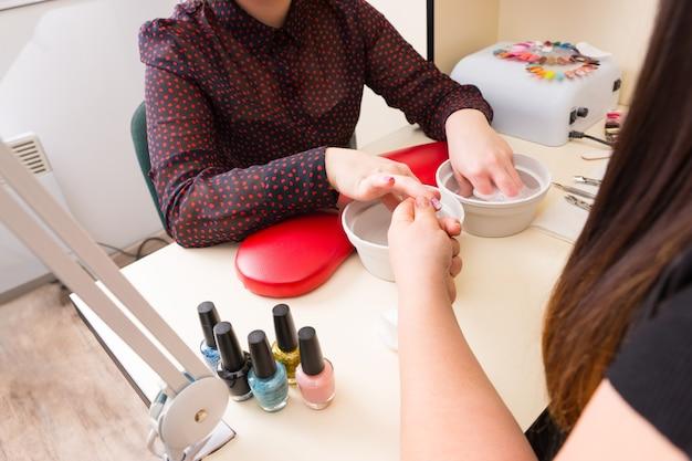 Close up de mulher irreconhecível fazendo manicure no spa - manicure preparando as unhas de uma cliente com as mãos imersas em água
