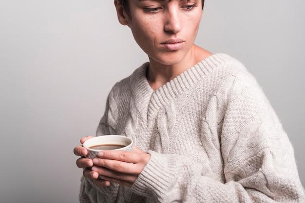Close-up, de, mulher jovem, desgastar, suéter, segurando, xícara café