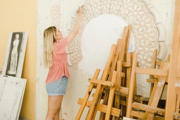 Close-up, de, mulher jovem, esculpindo, ligado, parede, com, ferramentas