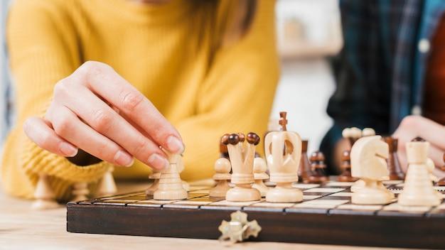 Close-up, de, mulher jovem, jogando xadrez, jogo tábua