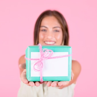 Close-up, de, mulher jovem, oferecendo, caixa presente, amarrada, com, cor-de-rosa, cadeia