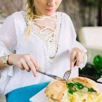 Close-up, de, mulher, mão, hambúrguer cortante, com, garfo, e, faca manteiga