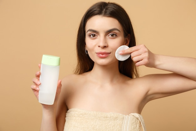 Close up de mulher morena seminua com pele perfeita, removendo maquiagem nude isolada em parede bege pastel