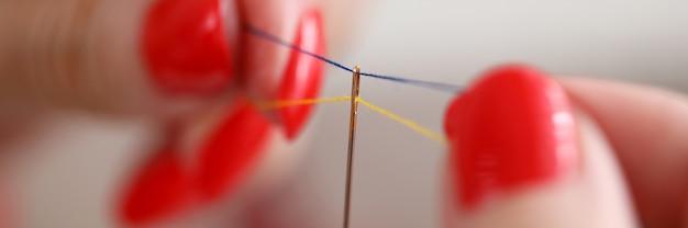 Close-up de mulher segurando fios azuis e amarelos na agulha.
