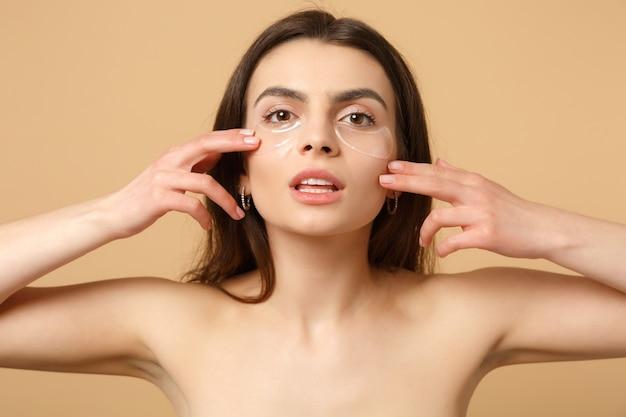 Close-up de mulher seminua com pele perfeita, manchas de maquiagem sob os olhos isoladas em parede bege Foto gratuita