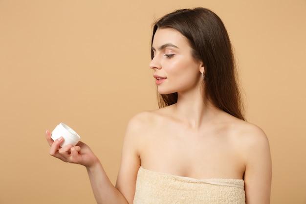 Close-up de mulher seminua com pele perfeita nude maquiagem aplicando creme facial isolado em parede bege pastel
