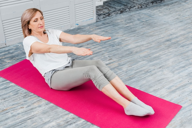 Close-up, de, mulher sênior, esticar, para, toque, dedos pé, enquanto, sentando, ligado, esteira yoga