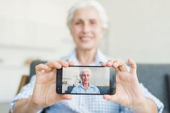 Close-up, de, mulher sênior, mostrando, dela, foto, ligado, smartphone