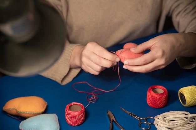 Close-up, de, mulher, stitching, plushie, coração