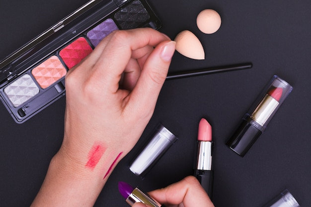 Close-up, de, mulher, tentando, a, batom, sombra, mão, contra, pretas, fundo
