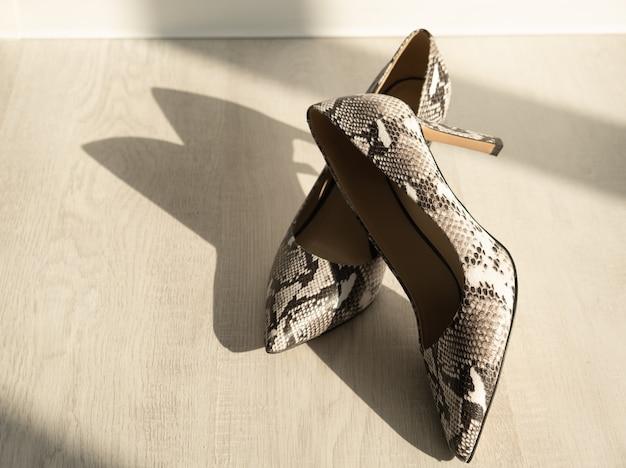 Close-up de mulheres cinzentas cobra sapatos de pele de couro com salto alto no chão claro na tarde ensolarada.