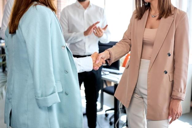 Close-up de mulheres de negócios apertando as mãos iniciando a colaboração em negociações de grupo