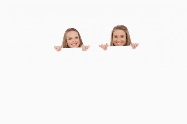Close-up de mulheres jovens atrás de um sinal em branco